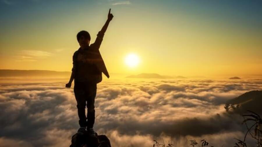 person-raising-hand-mountain